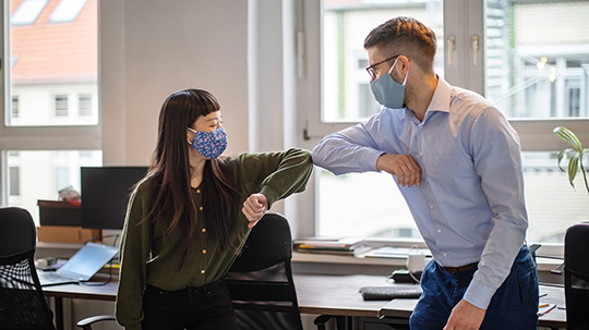 Two co-workers, wearing face masks, bumping elbows