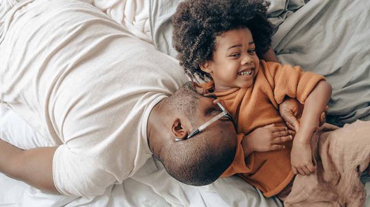 Father and child playing on a bed