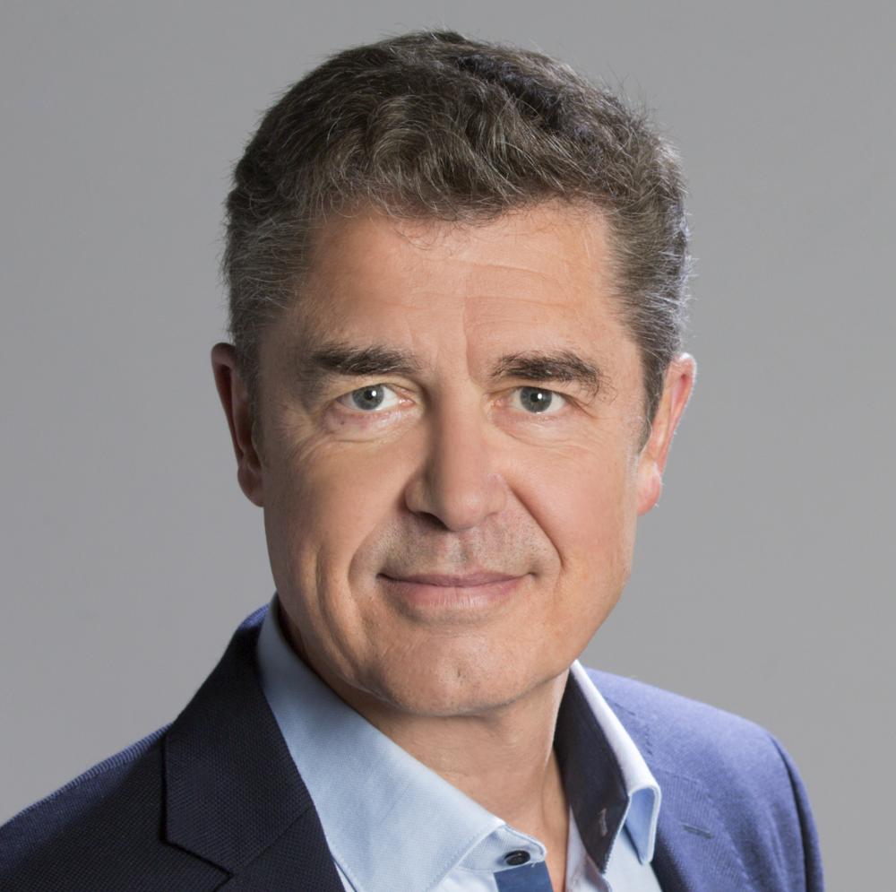 Dr. Stefan Eßer: ein lächelnder Mann mit kurzen lockigen Haaren